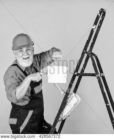 Painter In Overall And Cap With Paint Bucket. Builder Worker Painting Facade. Thermal Insulation Wor