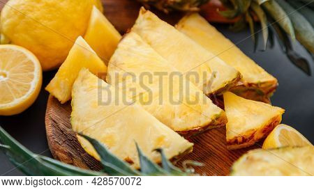 Pineapple On Cutting Board. Summer Fruit Sliced Pineapple Slicing Process In Kitchen On Dark Backgro