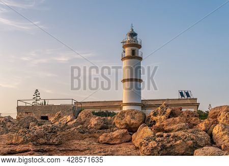 Lighthouse Of The Mallorcan Town Of Ses Salines At Sunset In Summer. Golden Hour