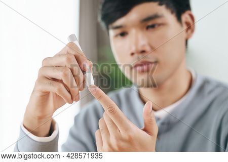 Man Using Lancet On Finger For Checking Blood Sugar Level By Glucose Meter, Healthcare And Medical,