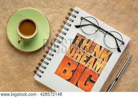 think and dream big motivational phrase -  word abstract in letterpress wood type in a notebook with coffee