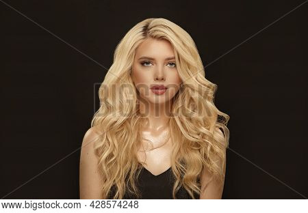 Blonde Woman With Long Curly Hair, Beauty Shot In Black Background.
