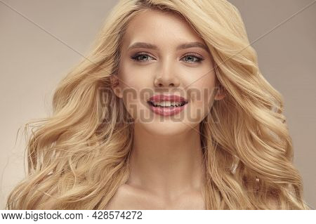 Blonde Woman With Long Curly Beautiful Hair Close Up.