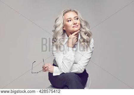 Lifestyle Of Maturity. Attractive Senior Woman On Gray Isolated Background Sitting On A Chair, Dream