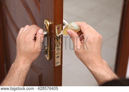 Repairman Lubricating Door Lock Indoors, Closeup View