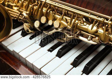 Beautiful Saxophone On Piano Keys, Closeup. Musical Instruments