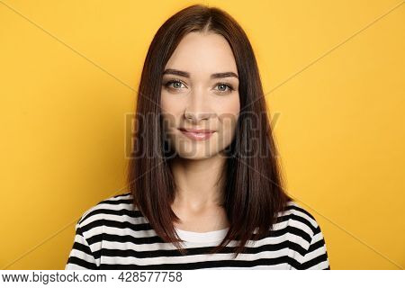 Portrait Of Pretty Young Woman With Gorgeous Chestnut Hair On Yellow Background