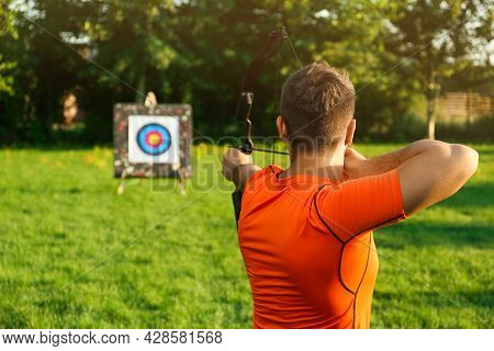 Man With Bow And Arrow Aiming At Archery Target In Park, Back View