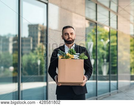 Man Is Upset By Dismissal, Lost His Job. Fired Male Worker Moving Out Office With Box Full Of Belong
