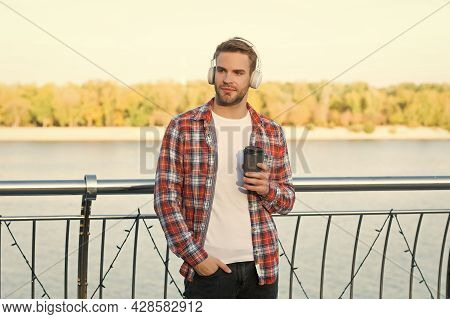 Unshaven Guy With Coffee Cup Outdoor. Male Casual Hipster Fashion. Man In Headset Listen Song. Music
