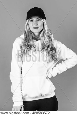 Sporty Woman With Blond Curly Hair In Cap And Hoody, Fashion