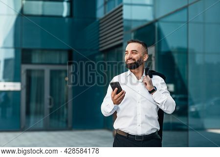 Handsome Mature Businessman Browsing Net On Cellphone During Coffee Break, Walking Near Office, Copy