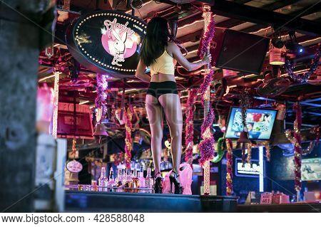 A Cute Sexy Thai Asian Girl Dances A Striptease On A Pole. Night Club In Thailand On The Street Of P