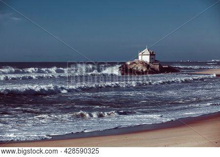 View of the Atlantic Ocean and Chapel Senhor da Pedra on the coast, Vila Nova de Gaia, Portugal.