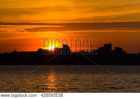 Amazing Golden Sunrise Or Sunset At The City. Black Silhouette Of The City On The Sea Shore. Colorfu