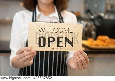 Portrait Of A Happy Woman Asian Waitress Standing At A Coffee Shop Holding Open Sign While Reopening
