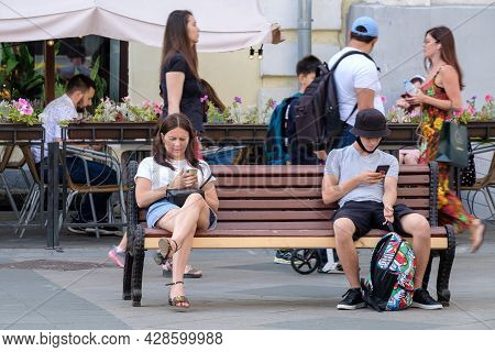 Moscow. Russia. August 1, 2021. Young Man And Woman Are Sitting On A Bench And Typing On Mobile Phon