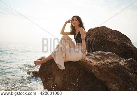 Woman Traveler Sitting Near Sea On Cliff Injoying View Of Sea And Nature