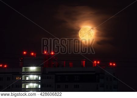 The Roof Of The House In The Light Of The Full Moon. Full Moon. A Yellow Moon Covered With Clouds Ov