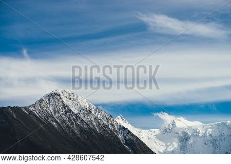 Atmospheric Alpine Landscape With Snow-covered Mountain Top Under Cirrus Clouds In Blue Sky. Awesome
