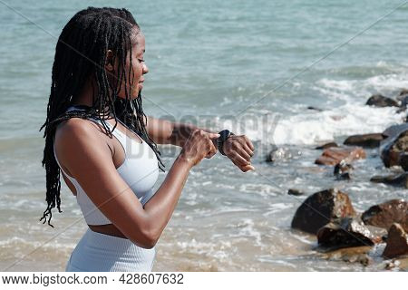 Beautiful Fit Young Sportswoman Standing On Beach And Checking Fitness Tracker On Her Smart Watch