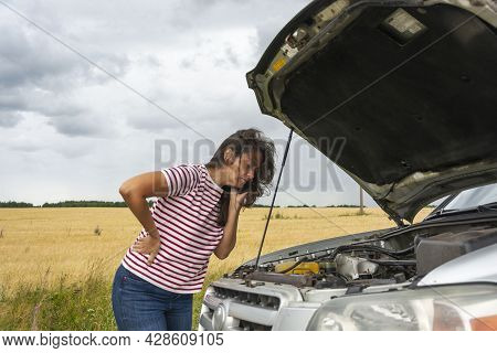 A Broken Car. A Young Woman Stands On The Road By A Broken Car Against The Background Of A Yellow Fi
