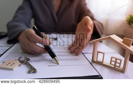 Realtor Real Estate Agent Pointing To Sign On The House Purchase Contract With The Model House, Keys
