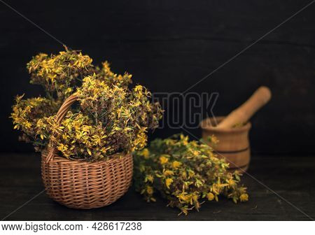 A Basket With Dried St. Johns Wort Grass And Fresh St. Johns Wort Grass And A Mortar On A Dark Woode