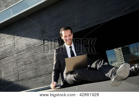 A Businessman Sitting On The Floor With A Laptop Computer, Rising His Arm