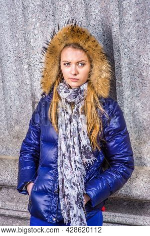 Teenage Girl. Dressing In A Blue Down Hooded Jacket With Trim Faux Fur, Hood Covering Head, Long Sca