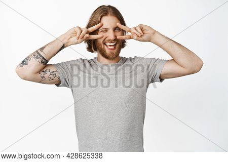 Happy Handsome Blond Man In Grey T-shirt, Showing Kawaii, Peace V-signs Near Eyes, Winking And Smili
