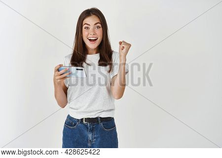 Happy Attractive Brunette Girl Joying Win In Video Game On Smartphone, Isolated Over White Backgroun