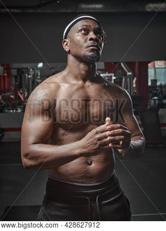 Sports African American Guy With Naked Muscular Torso Posing In Gym. Personal Sportive Trainer With