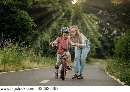 Mother Teaching Son To Ride Bicycle. Happy Cute Boy In Helmet Learn To Riding A Bike On The Bike Pat
