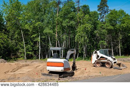 A Compact Front Loader And Mini Excavator Sits On The Dirt At A New Home Construction Lot, With Tree