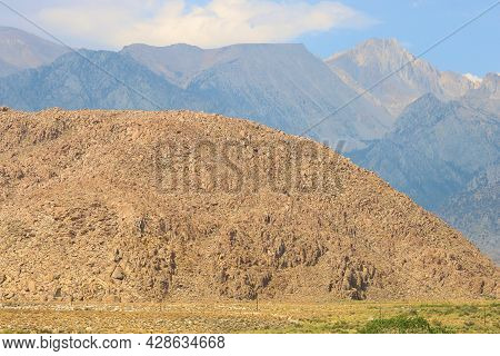 Rocks And Boulders On Arid Badlands With The Rugged Sierra Nevada Mountains Beyond Taken At The Alab
