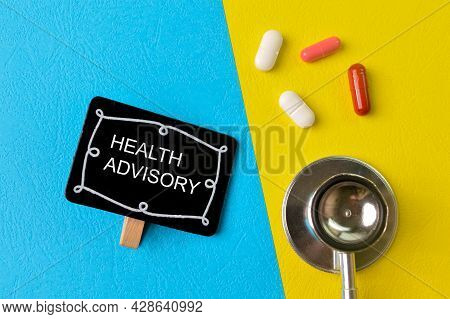 Stethoscope, Pill Capsules And Wooden Clip With Text Health Advisory