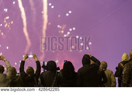View From The Back At People In Wark Clothes Shooting Fireworks On The Phone At Cold Night.