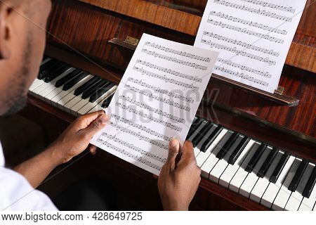 African-american Man With Note Sheets At Piano, Closeup. Talented Musician