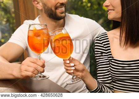 Couple Clinking Glasses Of Aperol Spritz Cocktails At Table, Closeup