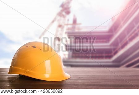 Hard Hat On Wooden Surface At Construction Site With Unfinished Building. Space For Text