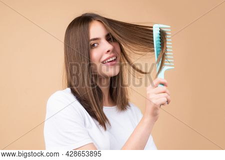 Girl Combing Hair. Beautiful Young Woman Holding Comb Straightened Hair. Attractive Smiling Woman Po