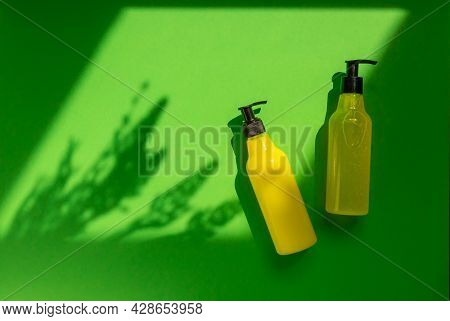 Plastic Mock-up Of Yellow Cosmetic Bottles With Shadow Flowers On A Green Background. A Creative, Mi