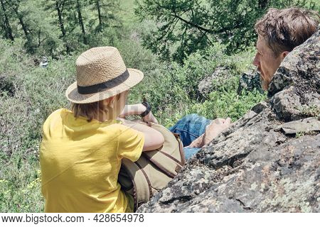 Father And Son Sit On A Stone High In The Mountains And Admire The Beautiful Nature. Back View. Calm