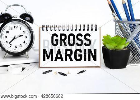 Profit Margin, A Notebook On A Work Table, Near A Desk Clock, A Flowerpot And A Glass With Pencils