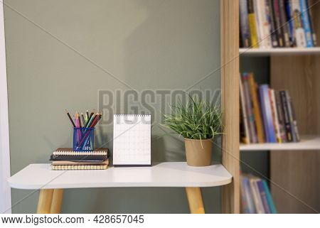 Desk For Student Education Concept. Book, And Pencil For Study For Exam. Calendar And Green Plant Pl