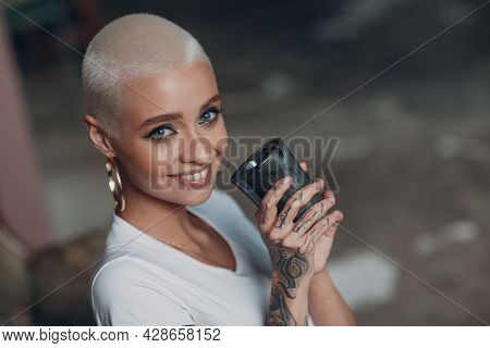Millenial Young Woman With Short Blonde Hair Portrait Sitting And Smiling With Cup Of Tea Or Coffee