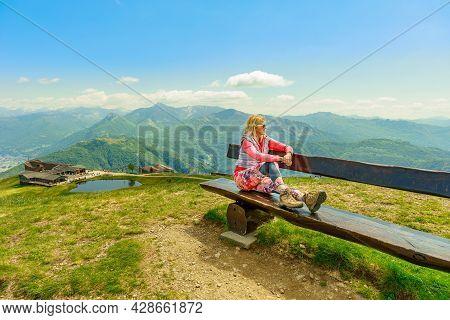 Backpacker Woman In A Trekking Dress Enjoying Tamaro Mount In Switzerland. Swiss Bench By The Pond I