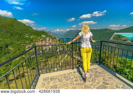 Elegant Woman On Top Of Lugano Swiss City By Lugano Lake In Switzerland. Aerial View Lookout From Mo