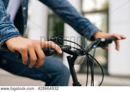 Close-up Hands Of Unrecognizable Cyclist Male Pressing Handlebars On Handlebars Of Bicycle Outdoors